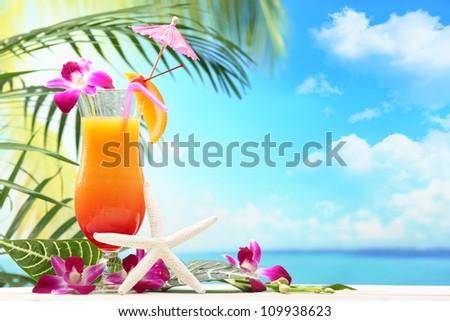 Refreshing orange cocktail on beach table. - stock photo