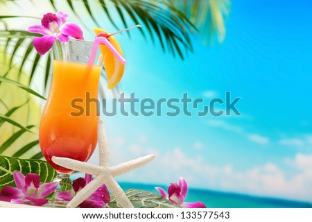 Refreshing orange cocktail on beach table. - stock photo