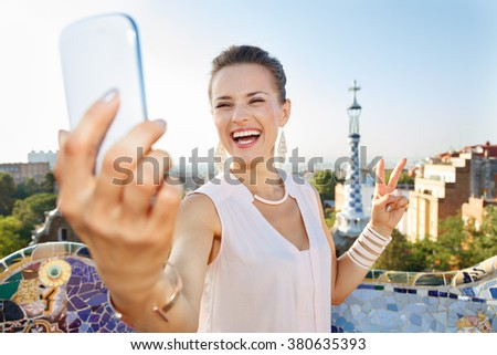 Refreshing promenade in unique Park Guell style in Barcelona, Spain. Portrait of smiling young woman showing victory gesture and taking selfie with smartphone while in Park Guell, Barcelona, Spain - stock photo