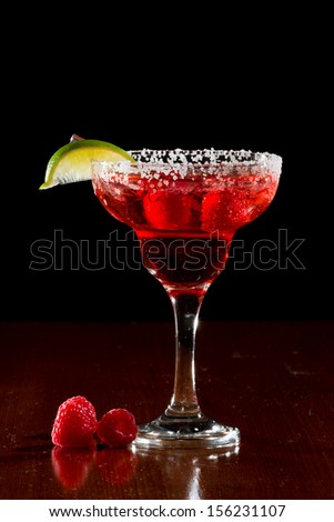 refreshing raspberry margarita isolated on a black background garnished with a lime wedge - stock photo