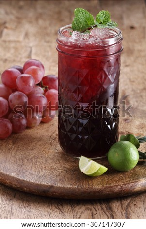 refreshing red grape beverage in glass on wooden background  - stock photo
