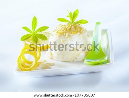 Refreshing sour lemon sorbet dessert served with coiled lemon zest on a square porcelain platter - stock photo