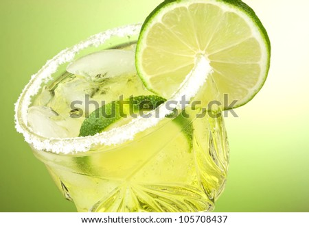 Refreshing summer cocktail drink with limes and ice isolated on green gradient background with copy space. - stock photo