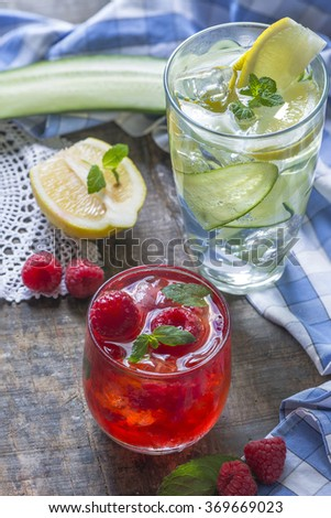 Refreshing summer cocktails - Raspberry Crush and Gin and Tonic with Cucumber in the background - stock photo
