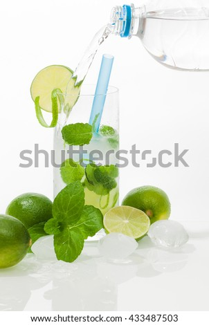 Refreshing summer drink; Glass of ice-cold water, flavored with lime slices and mint leaves against white background; Low-calorie drink for diet and fluid balance - stock photo
