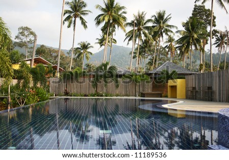 Refreshing swimming pool in an exotic health resort. Leisure and relaxation concept. - stock photo