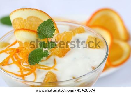 Refreshing yogurt dessert with oranges on white background. Shallow DOF - stock photo