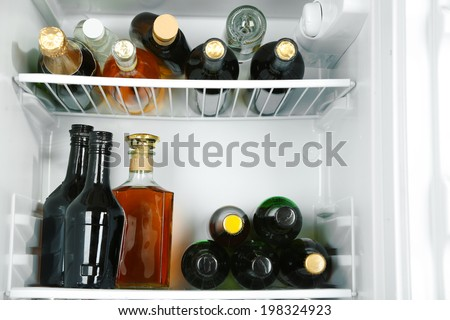 Refrigerator full of bottles with alcoholic drinks - stock photo