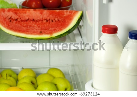 Refrigerator full with some kinds of food - fruits, vegetable and milk - stock photo