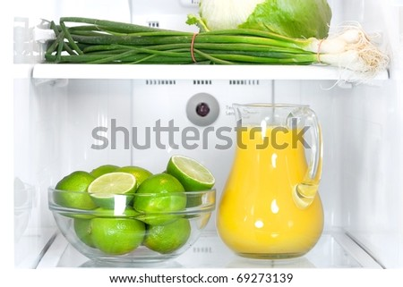 Refrigerator full with some kinds of food - orange juice, lime, onion - stock photo