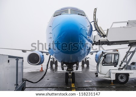 refueling a plane on the airport, bad weather and fog - stock photo
