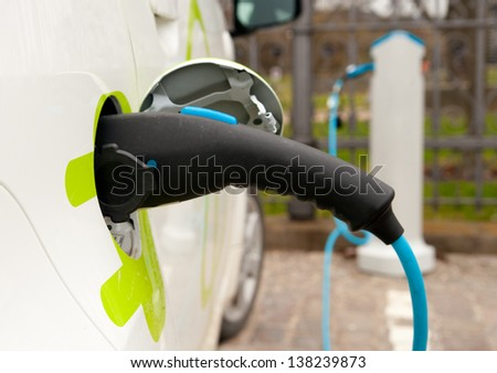 Refueling an electric car, an environment friendly alternative - stock photo