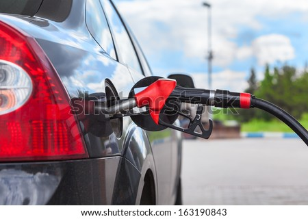 Refueling vehicle with gasoline at city gas station - stock photo