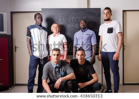 Refugees Welcome: A female German volunteer is proudly posing with young African (Gambia) and Arabic (Algeria and Tunesia) men she is teaching the German language in a refugee camp quickly errected - stock photo