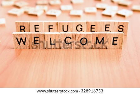 Refugees Welcome text on wooden tiles letters - stock photo