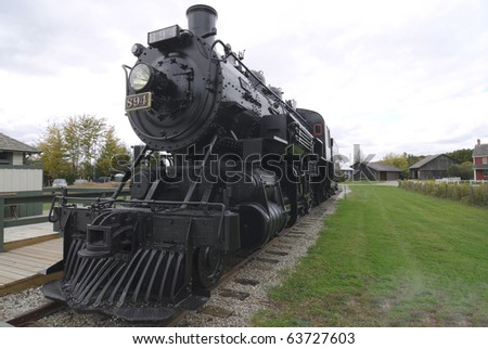 refurbished steam locomotive sitting on tracks in rail museum - stock photo