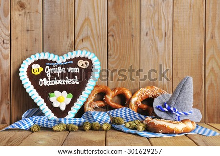 regards from the Oktoberfest  - original bavarian gingerbread heart with Oktoberfesthat and soft pretzels from Germany in front of olt wooden board - stock photo