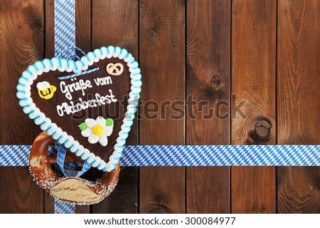 regards from the Oktoberfest - original bavarian salted soft pretzel and Oktoberfest gingerbread heart from Germany in front of wooden board - stock photo