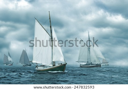 Regatta of old sailing boats coming out of the fog. - stock photo