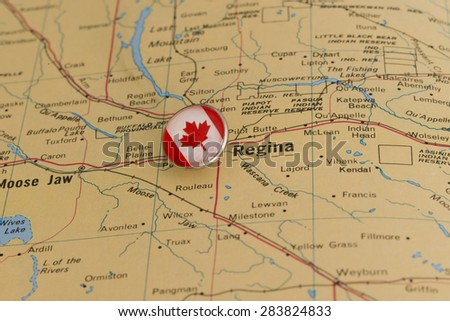 Regina marked with national flag pushpin on map. Selected focus on Regina and pushpin.  - stock photo
