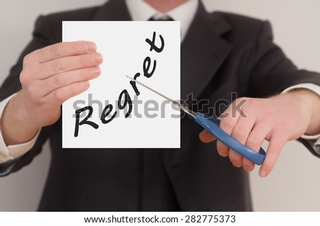 Regret, man in suit cutting text on paper with scissors - stock photo