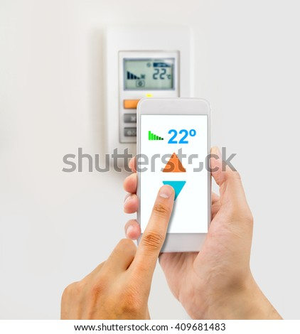 regulating the temperature from the smartphone and controlling the digital thermostat with finger pressing button - stock photo