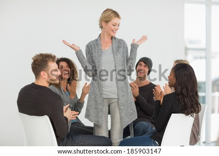 Rehab group applauding happy woman standing up at therapy session - stock photo