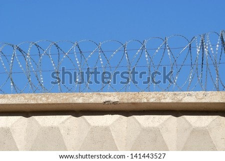 Reinforced concrete fence with barbed wire against the sky - stock photo