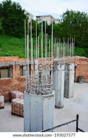 Reinforced concrete pillars and red brick masonry on house under construction. - stock photo