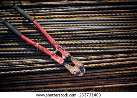 Reinforced steel bars and bolt cutter on building construction site - stock photo