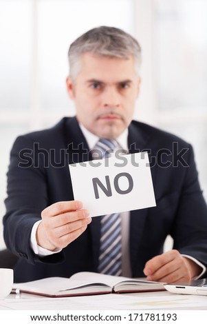 Rejected! Confident senior man in formalwear holding a paper with no sign on it while sitting at her working place - stock photo