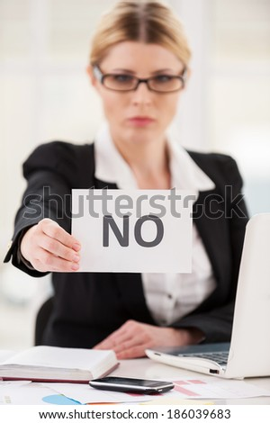 Rejection. Serious mature woman in formalwear saying no to you while stretching out a paper - stock photo