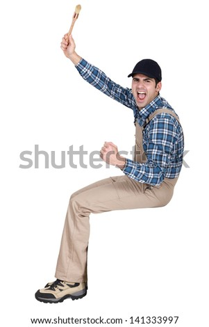 Rejoicing painter holding a stencil brush - stock photo