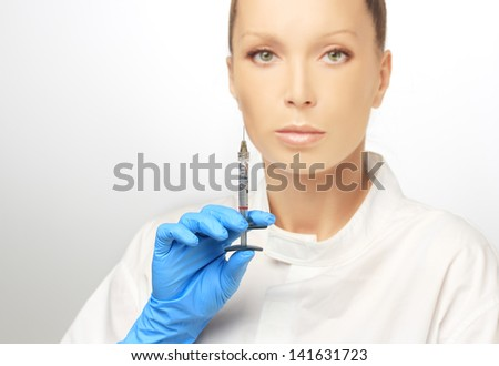 Rejuvenation.Attractive doctor prepare to Injection of beauty products.Looking at camera,selective focus - stock photo