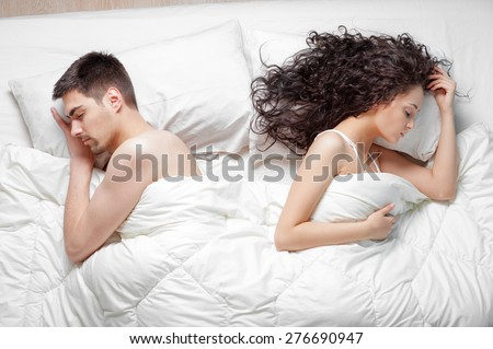 Relationship concept. Top view of young couple lying on the bed. - stock photo