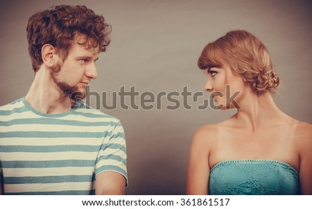Relationship concept. Woman and man sitting on couch looking serious to each other face to face - stock photo