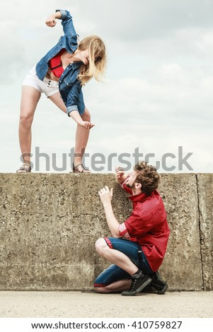 Relationship concept. Woman and man young couple in love playing fighting, angry fury girlfriend screaming outdoor on sky background - stock photo