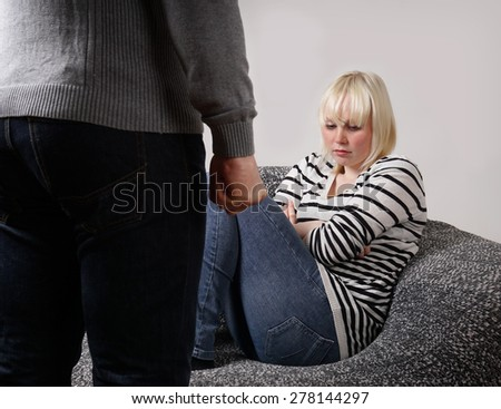 relationship difficulties man with clenched fist standing in front of defensive young woman                          - stock photo