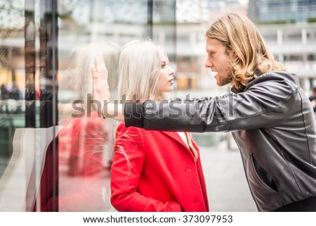 Relationship issues - Couple arguing outdoors - Stalker attacking a beautiful woman - stock photo