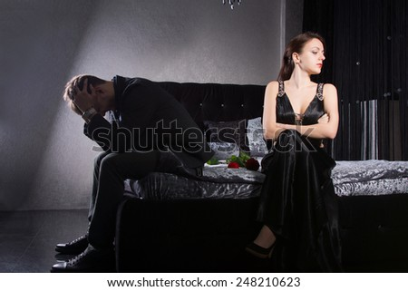 Relationship Problem Concept - Young Couple in Formal Clothes Quarreling While Sitting at the Bedroom - stock photo