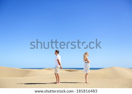 Relationship problem - upset couple argument. Angry couple in disagreement divorce and separation concept. Young couple with marriage problems. Woman and man conceptual image in desert under blue sky. - stock photo