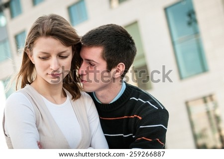 Relationship problems - man trying to reconcile with offended woman - stock photo