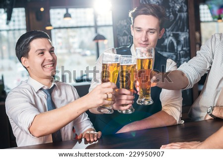 Relax after work. Three cheerful friends met at the bar and clink glasses of beer while the bartender is standing on the bar. Friends having fun together - stock photo