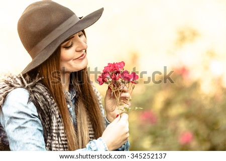 Relax and gardening. Lovely cute young woman spending time in garden. Cheerful beauty girl with pink flowers outdoor. - stock photo