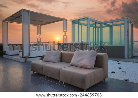 Relax coner on condominium roof top garden with sofa and table - stock photo