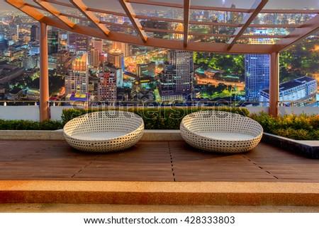 Relax corner on condominium rooftop garden with chairs on landmark bangkok top view at night background, Landmark concept - stock photo
