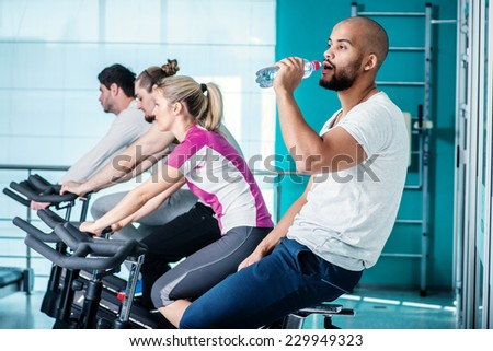 Relax in the gym. Young boy sitting on a stationary bike and drinking water while his three friends pedal in the gym - stock photo