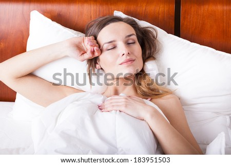 Relax time in bed - sleeping young woman - stock photo