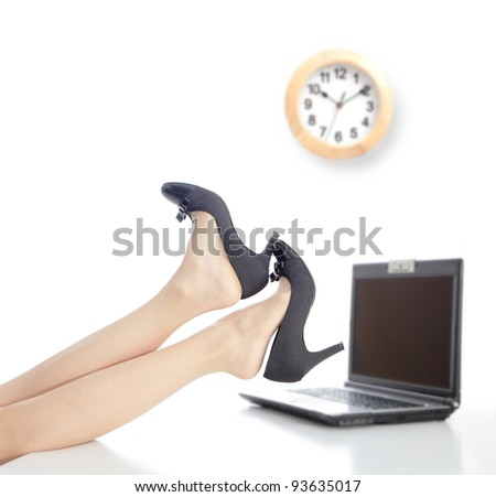 Relax Time in office, business woman take off high heels shoes with office background and a clock - stock photo