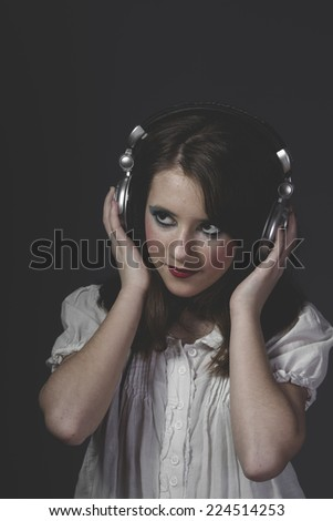 Relax, young girl listening music with huge headphones - stock photo
